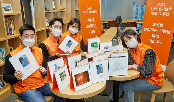 한화봉사단 임직원들이 점자달력을 소개하며 기념촬영